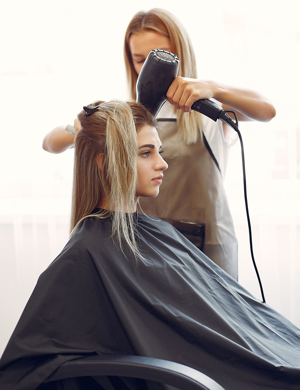 Hairdresser drying head her client. Woman in a hair salon